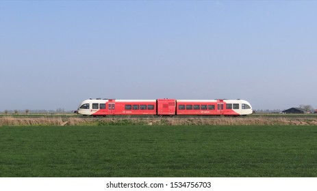 Boazum / Netherlands - April 8 2019: A red/white Arriva diesel local passenger train on the countryside of Friesland