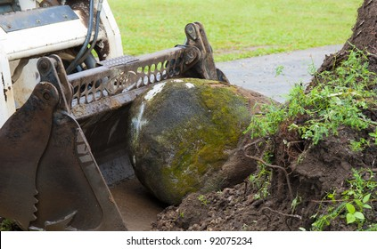 a bob cat moving a large garden rock