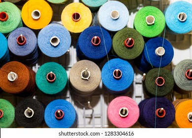 Bobbins with colorful threads on old wooden table background, Sewing background.Interior of sewing workshop.technology, material, equipment, Hobby concept.spools of thread.