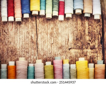 Bobbins with colorful threads on old wooden table background, Sewing background
