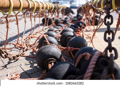 Bobbins and floats for bottom trawling with a trawl fishing net, drying on a street in a harbor in Urk, the Netherlands