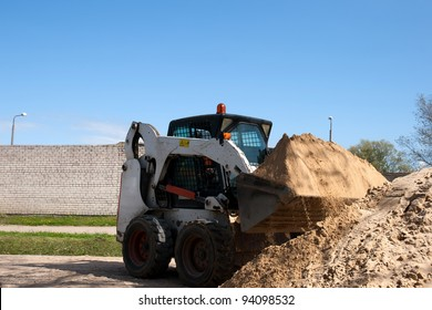 A bobcat doing some construction work with sand