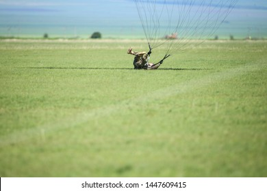 Boboc, Romania - May 22, 2019: Romanian military paratroopers land after jumping from an army plane, during a drill.