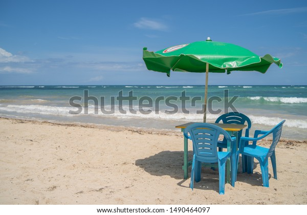 BOCA CHICA/DOMINICAN REPUBLIC - JULY 7, 2019: Green Presidente's beer beach umbrella covering blue plastic chairs in a sunny day at sea's shore.