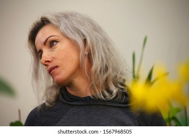 BOCA RATON, FLORIDA / USA - NOVEMBER 17 2019:  Woman surveys orchids with a pensive look in a seasonal show.