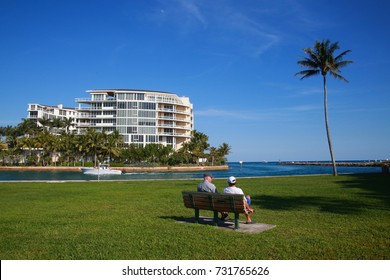BOCA RATON, FLORIDA/USA - FEBRUARY 5 2017  Two men sit on a park bench in front of the Intracoastal Waterway next to Boca Beach Place as a boat passes by in a clear sunny afternoon.