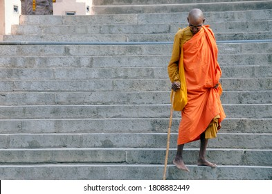 bodh gaya bihar india on april 29th 2018 : old buddhist monk walking down through stairs at mahabodhi temple complex bihar india.