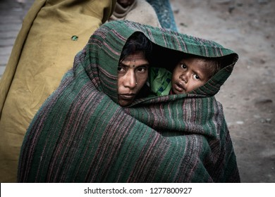 Bodh gaya, India -January 7, 2019 : An unidentified beggar mother and kids waiting the tourist to give them money. on the street in Gaya, India