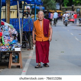 Bodhgaya, India - Jul 9, 2015. A Buddhist monk walking on street in Bodhgaya, India. Bodh Gaya is considered one of the most important Buddhist pilgrimage sites.