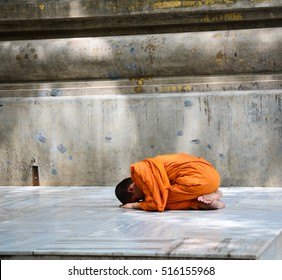 Bodhgaya, India - Jul 9, 2016. A young monk praying on his knees at Mahabodhi Temple in Bodhgaya, India.