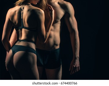 Bodies of woman and man. Sexy girl back with buttocks in black panties and pantyhose on dark background. Strong male torso with six pack, ab and hands with biceps, triceps. Passion and desire