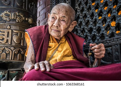 Bodnath, Kathmandu, Nepal- September 09 2017: Portrait of an old Nepalese buddhist nun praying in front of Bodnath stupa, Kathmandu, Nepal.