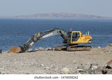 BODO, NORDLAND COUNTY / NORWAY - AUGUST 03 2019: Yellow excavator on a construction site against blue sea
