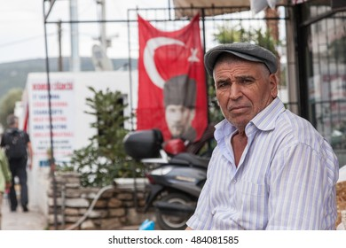 Bodrum, Turkey, circa October 2015. Man by his private house with Turkish national symbols- a national flag with a portrait of Ataturk. The symbols are present everywhere in the country.