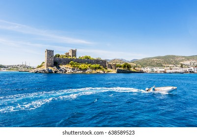 Bodrum, Turkey - May 11, 2017 : Fisherman is driving a boat front of Bodrum Castle. Bodrum is populer tourist destination in Turkey.