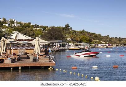 BODRUM/TURKEY - SEPTEMBER 24, 2016: Luxury, expensive, famous beach clubs in Turkbuku town of Bodrum peninsula. People take sunbath.