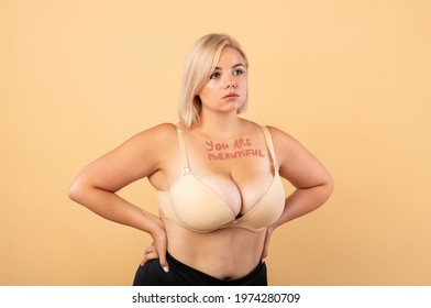 Body Acceptance. You are beautiful motivational inscription on chest of plus size woman, curvy young lady in bra posing over beige studio background, keeping hands on waist and looking away