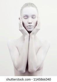 Body art nude woman. conceptual halloween make-up. painted white powder skin beauty girl