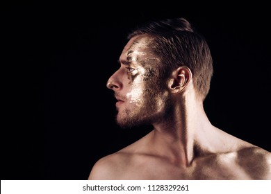 body art paint with gold on face of man. man has golden body art. body art concept. luxury body art on face of man isolated on black background, copy space. Add some color to your life