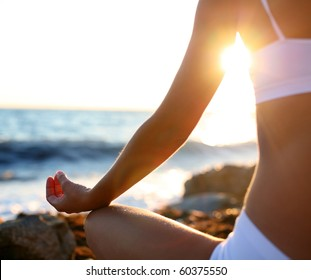 Body of a beautiful girl in a meditation on the beach. Lotus pose.