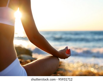 Body of beautiful girl in a meditation on the beach. Lotus Pose. Welness background. Spa concept.