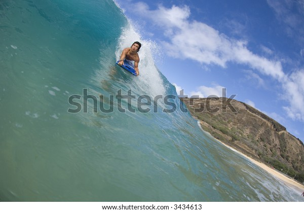 body boarder riding wave in hawaii in contest