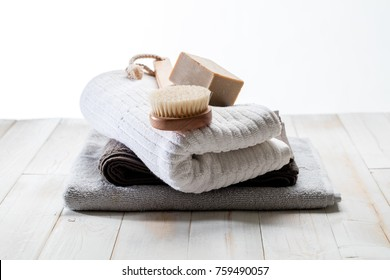 body brush, solid soap and pile of cotton towels for green friendly shower or traditional bath concept over white wood background, still life in studio
