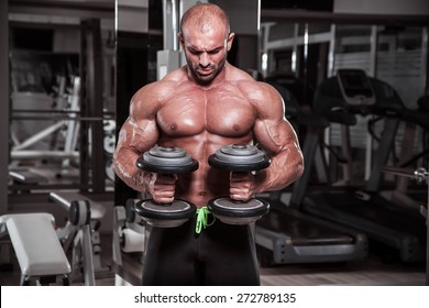 Body Builder performing exercise for biceps with weights in both hands.