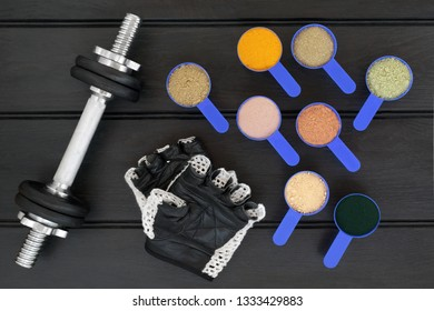 Body building dumbbell weights and gloves with dietary food supplement powders. Top view on wood table.