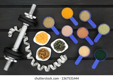 Body building dumbbell weights and tape measure with dietary food supplement powders,  multi vitamin and chlorella tablets with fish oil capsules. Top view on wood table.