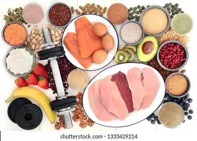 Body building health food and dumbbell weights with high protein meat, fish, nuts, seeds, legumes, grains, dairy, dietary supplement powders, multi vitamin & chlorella tablets, vegetables and fruit.
