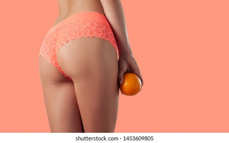 Body care and anti cellulite massage. Beautiful slim woman is holding orange. Perfect female buttocks on coral background.