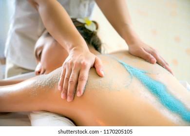 Body care.  Beautiful young woman brunette Getting a Salt Scrub Beauty Treatment in the Health Spa. Body Scrub.