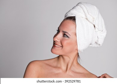 Body Care. Beautiful young woman posing in white towel. Spa, healthcare. isolated on grey background