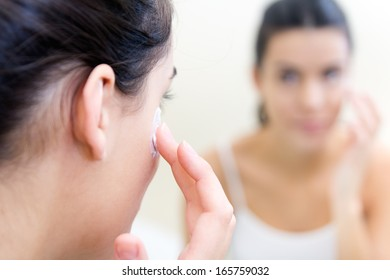 Body care. Close up portrait of Woman applying cream on face