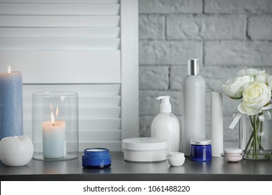 Body care cosmetics and burning candles on table