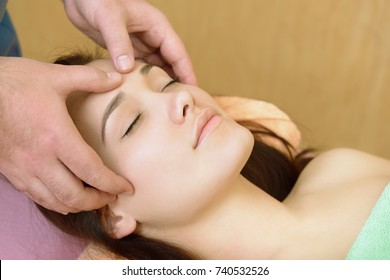 Body care. Face massage. Beautiful young woman relaxing with hand massage at beauty spa salon.