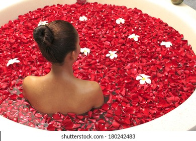 Body care female in bath with rose petal