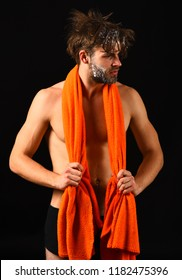 Body care. Man with orange towel on neck ready to take shower. Macho attractive nude guy black background. Man bearded tousled hair covered with foam or soap suds. Wash off foam with water carefully.