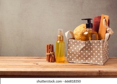 Body care and personal hygiene products on wooden table over grey background