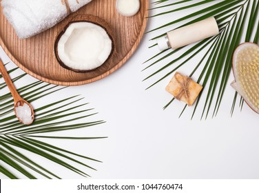 Body care producs, coconut and green leaves. Tropical spa concept.