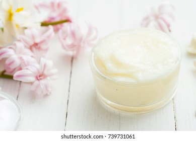 body care products with hyacinth and daffodil flowers on white wooden table background