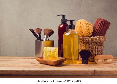 Body care products on wooden table over gray background