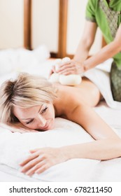 Body care. Spa body massage treatment with hot herbal ball for deep relaxation . Woman having massage in the spa salon