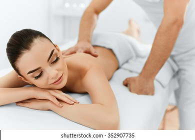 Body Care. Spa Woman. Beauty Treatment Concept. Masseur Doing Hand Massage On Relaxed Beautiful Young Caucasian Woman's Body In The Spa Salon. Skin Care, Wellness, Wellbeing.