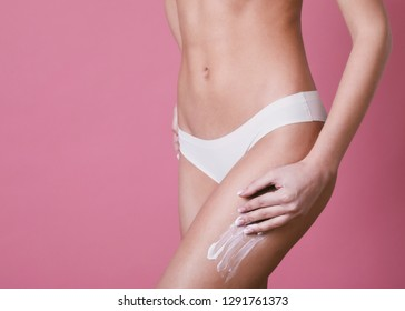 Body care. Woman applying cream on legs and buttocks.