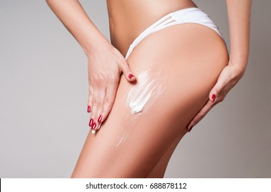 Body care. Woman applying cream on legs and buttocks. Female applying cosmetic cream from cellulite