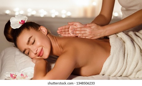 Body care. Woman enjoying relaxing back massage in spa centre