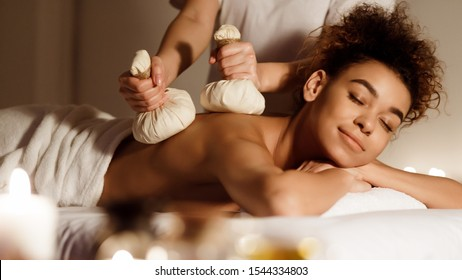 Body care. Woman having Thai herb compress massage in beauty spa