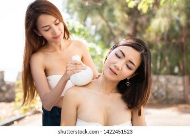 Body care. Young Asian Woman having massage with hot herbal balls for deep relaxation ,soft focus on hand.
